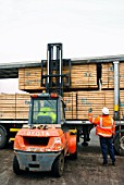 Forklift lifting timber onto an articulated lorry on the dockside at a port in Newport, South Wales, UK