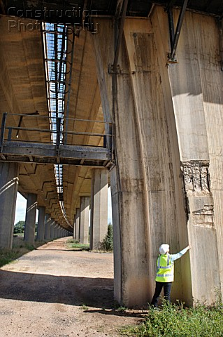 A female surveyor inspects damage to the reinforced concrete supports of a motorway bridge UK
