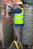 An electrician removes old electricity fuse boxes and installs a memera consumer unit, UK