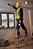 A plasterer on stilts skimming a ceiling on a cottage under renovation, UK