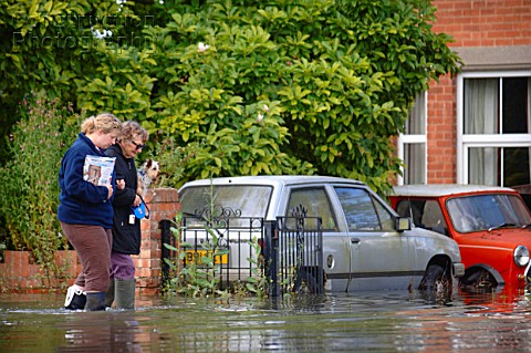 A older lady with her pet dog is helped by a younger neighbor in a residential street under floodwat