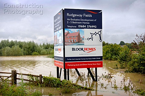 An advertising board for a planned housing development on land which is under floodwater in Tewkesbu