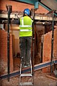 A workman fixes joist straps with acrow props and strong boys holding a supporting wall before a rsj is fitted to allow the enlargement of a wall opening