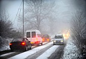 Cars driving carefully along snow covered road, UK