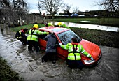 Firemen pulling stranded car out of flood water, Crudwell, Wiltshire, UK, Jan 2008