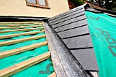 Section of slate roof under construction showing the breathable roofing felt with lead flashing valley and wooden batons