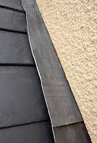 Slate roof joining a rendered wall with lead flashing