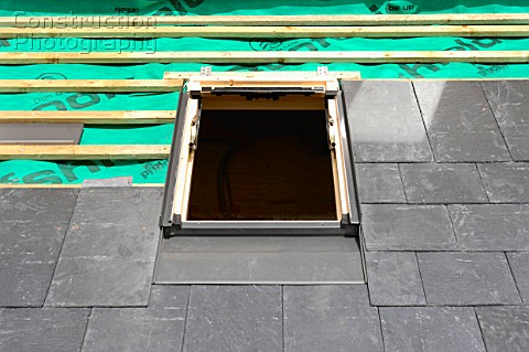 Fitting a velux window on a slate roof under construction showing the breathable roofing felt with w