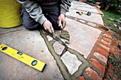 Man pointing patio with natural stone slabs, UK