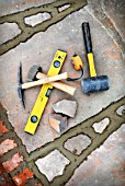 Builders tools amongst recently pointed joints awaiting brushing out on a patio laid with natural stone slabs, UK