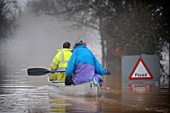 Two people canoeing past flood sign during floods, Gloucestershire, UK, 2007