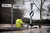 Man canoeing past signs during floods, Gloucestershire, UK, 2007
