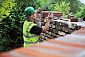 Using a spirit level during the building of a garden wall with cotswold stone and cement mortar UK
