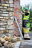 Building of a garden wall with cotswold stone and cement mortar UK