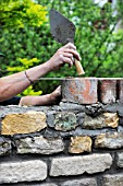 Building of a garden wall with Cotswold stone and reclaimed red bricks UK
