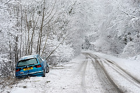 Abandoned car by side of road in snowy weather UK