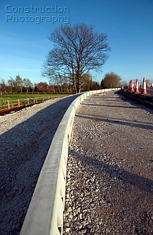 Halfbattered road kerbs being laid on a verges of a new road