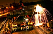 Motorway management. Demolition of a road sign at night. UK.