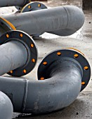 Group of large grey metal pipe elbow bends on concrete floor