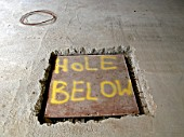 Warning painted on panel covering hole in new concrete floor screed