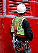 Back view of site worker in safety harness with tool belt