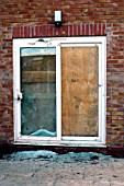 Vandalised French windows on new housing development.