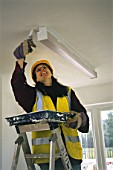 Woman decorating ceiling. Habitat for Humanity Self build project, Peckham, London