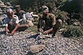 Three man breaking rocks with a hammer for the construction of the village road, Annapurna, Nepal, Himalaya.