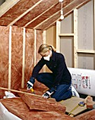 Insulating. Installing quilt loft-insulation to a roof space.