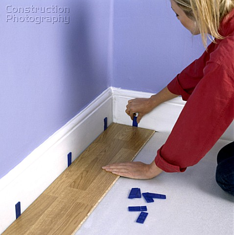 Woman laying new laminated floorboard