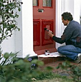 Painting a front door with bright red paint.