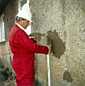 Builder repairing an external wall on a suburban property, housing estate, Croydon