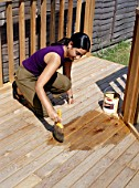 Woman applying varnish on a wooden deck.