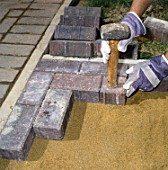 Laying paving stones in a front garden.
