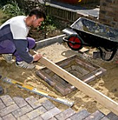 Laying paving stones around a manhole in a front garden.