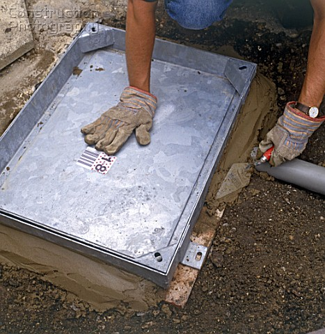 Installing a manhole cover over the drain