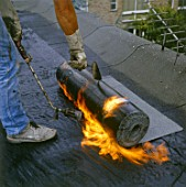 Bituminous Roofing. Applying bitumen roll on a flat roof.
