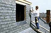 Roofer putting tiles on a roof extension
