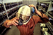 A miner puts on his hard hat and light in the lamp room, Tower Colliery, Hirwaun, South Wales