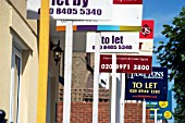 Estate Agent boards in front of houses, London.