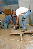 Builders cutting MDF with circular saw