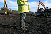 Legs of site warden with tracked excavator on landfill.