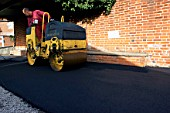 Spreading and rolling hot asphalt using vibratory roller.