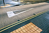 Coloured asphalt applied on road crossing with feature for blind pedestrians. England, UK.