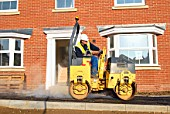 Hard landscaping in progress on a new residential development in South East England. Man driving a roller on asphalt pavement.