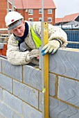 A bricklayer checking the levels on a wall - house building site, UK.
