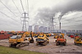 Plant hire equipment for sale on auction yard with power station in background, England, UK.