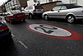 Speed limit road marking in a suburban street, London, UK