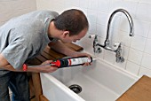 Man using sealant gun in a kitchen