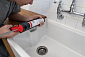 Man using sealant gun in bathroom